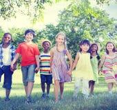 Verschiedene Kinderfreundschaft, die draußen Konzept spielt Stockbild