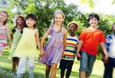 Verschiedene Kinderfreundschaft, die draußen Konzept spielt Stockfotos