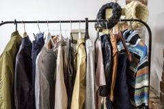 Verschiedene Kleidung und Taschen auf den Regalen und den Aufhängern Lizenzfreie Stockfotos