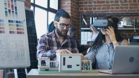 Verschiedene Kollegen, die VR beim Konstruieren des Hauses verwenden stock footage
