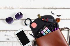 Verschiedene kosmetische Produkte und Kosmetik in der Umhängetasche stockfotos