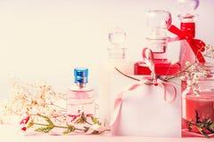 Verschiedene kosmetische Produktflaschen und -gläser mit Blumen und leeren Papierkarte mit Band für Einladung, Kupon, Rabatt und  Lizenzfreies Stockfoto