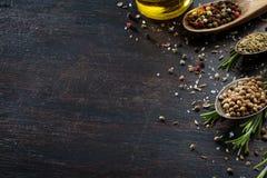 Verschiedene Kräuter und Gewürze auf dunkler hölzerner Tabelle Stockfotografie