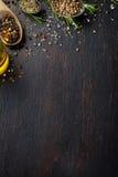 Verschiedene Kräuter und Gewürze auf dunkler hölzerner Tabelle Stockfotos