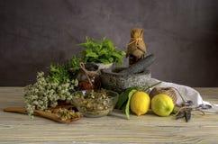 Verschiedene Kr?uter und Gew?rze, Zitronen und Oliven?l auf einem Holztisch stockfotografie