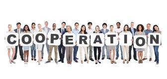 Verschiedene Leute, die Buchstaben halten, die die Zusammenarbeit bilden Lizenzfreie Stockfotos