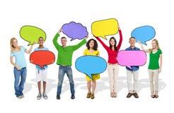 Verschiedene Leute, die bunte Sprache-Blasen halten Stockbild