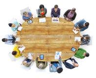 Verschiedene Leute, die um den Konferenztisch arbeiten Stockbild