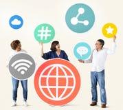 Verschiedene Leute mit Social Media-Ikonen Stockbild