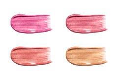 Verschiedene Lipglösser lokalisiert auf Weiß Befleckte Lippenglanzprobe Stockfotografie