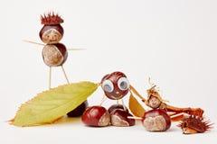Verschiedene lustige Kastanienzahlen gemacht von den Kastanien und von den Blättern Stockbild