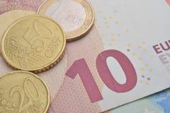 verschiedene Münzen und Eurobanknoten Stockfotografie