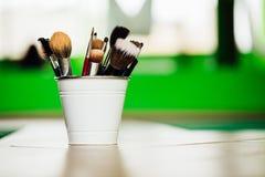 Verschiedene Make-upbürsten und -bleistifte auf hellgrünem Hintergrund innerhalb des Eimers der Boden Copyspace Stockbild