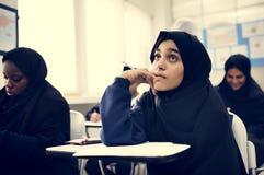 Verschiedene moslemische Kinder, die im Klassenzimmer studieren stockfotografie