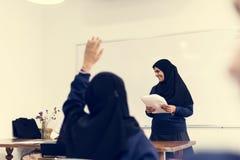 Verschiedene moslemische Mädchen, die im Klassenzimmer studieren lizenzfreie stockfotos