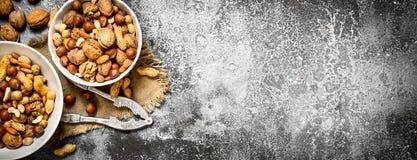 Verschiedene Nüsse in einer Schüssel mit einem Nussknacker Lizenzfreie Stockfotos