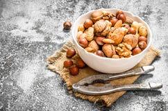 Verschiedene Nüsse in einer Schüssel mit einem Nussknacker Stockbilder