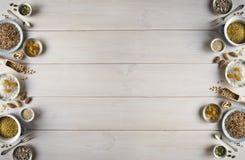 Verschiedene Nüsse, Getreide, Rosinen auf Platten auf einem Holztisch Zeder, Acajoubaum, Haselnuss, Walnüsse, Mandeln, Kürbiskern stockfotos