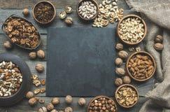 Verschiedene Nüsse und Schieferbrett Stockfotos