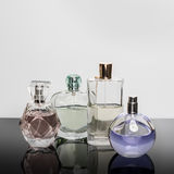 Verschiedene Parfümflaschen mit Reflexionen Parfümerie, Kosmetik Stockfotografie