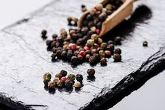Verschiedene Pfeffergewürze auf einem schwarzen Schiefer Bestandteile für das Kochen Gesundes Essenkonzept Verschiedene Gewürze a Lizenzfreies Stockbild