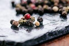 Verschiedene Pfeffergewürze auf einem schwarzen Schiefer Bestandteile für das Kochen Gesundes Essenkonzept Verschiedene Gewürze a Lizenzfreie Stockbilder
