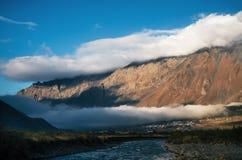 Verschiedene Schichten Wolken über Stepantsminda-Dorf und Berg, Georgia Stockbild
