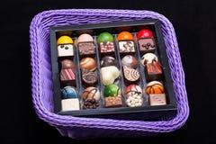 verschiedene Schokoladenpralinen im Lavendelkorb Stockbilder