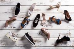 Verschiedene Schuhe, die auf Boden legen Stockbild