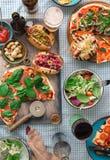 Verschiedene selbst gemachte Pizza, verschiedene Hotdoge, Wein, Bier und Snack Lizenzfreies Stockfoto