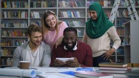 Verschiedene Studenten, die lustigen Inhalt auf Tablette grasen stock video footage