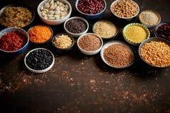 Verschiedene superfoods in den smal Schüsseln auf dunklem rostigem Hintergrund lizenzfreie stockbilder