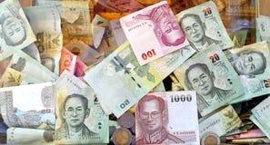 Verschiedene thailändische Banknoten und Münzen im transparenten Spendenkasten Lizenzfreie Stockbilder