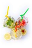 Verschiedene Tipps der Limonade im Krug mit Strohen und Zitronen auf weißem Hintergrund Lizenzfreie Stockfotos