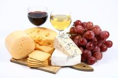 Verschiedene Typen des Käses, des Weins, der Trauben und der Cracker Stockfotos
