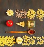 Verschiedene ungekochte Teigwaren und hölzerner Löffel mit Gewürzen auf dunklem Hintergrund stockfotografie