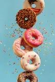 Verschiedene verzierte Donuts in der Bewegung, die auf blauen Hintergrund fällt lizenzfreie stockfotografie