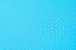 Verschiedene Wassertropfen auf blauem Hintergrund, Abschluss oben stockbilder