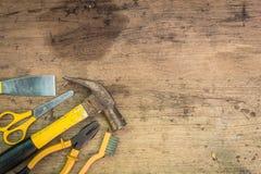Verschiedene Werkzeugversorgungen auf einem hölzernen Hintergrund Stockfotografie