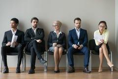 Verschiedene Wirtschaftlerbewerber, die in ReihenwarteVorstellungsgespräch sitzen lizenzfreies stockfoto