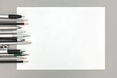 Verschiedene Ziehwerkzeuge und leeres Blatt Papier auf grauem Bürode Lizenzfreie Stockfotografie