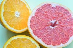 Verschiedene Zitrusfrüchte: Pampelmuse, orange auf grünem Hintergrund Stockbild