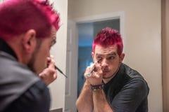 Verschiedener kaukasischer Mann mit dem ährentragenden rosa Haar, das Eyeliner im Spiegel anwendet stockbilder
