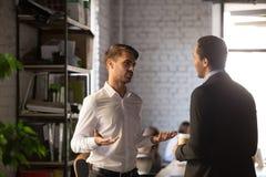 Verschiedener männlicher Firmenmitarbeiter, der im Büro und in der Unterhaltung steht lizenzfreies stockfoto