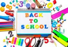 Verschiedener Schulbedarf lokalisiert auf weißem Hintergrund Notizbuch in der Mitte des Rahmen Konzeptes zurück zu Schule stockbild