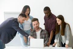 Verschiedenes Arbeitsteam, das am Laptop während der Sitzung zusammenarbeitet lizenzfreies stockbild