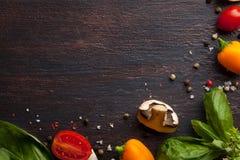 Verschiedenes Gemüse und Kräuter auf dunkler hölzerner Tabelle Stockfotografie