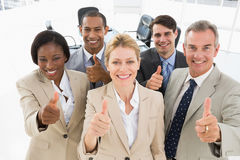 Verschiedenes nahes Geschäftsteam, das oben an der Kamera aufgibt Daumen lächelt stockfoto