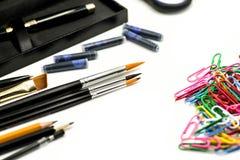 Verschiedenes stationäres in den schwarzen Farben und bunten in den Büroklammern lokalisiert auf Weiß Stockfotos