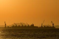 Verschiffungshafen im Meer mit Sonnenunterganghimmel Stockbilder